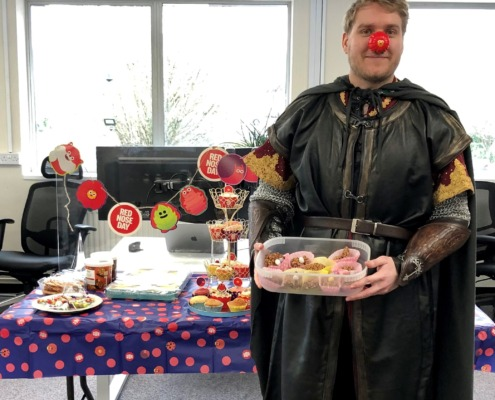 Impact staff member, Scott posing in his costume with the cakes